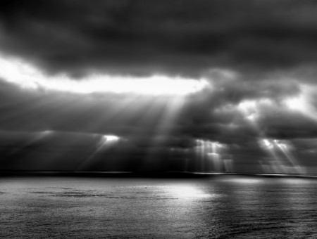 Sunlight Through Clouds With View Of Ocean Water In Grayscale Photography