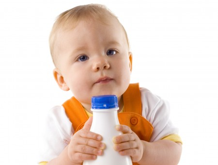 Baby In Orange Dungarees Holding A Glass Of Milk