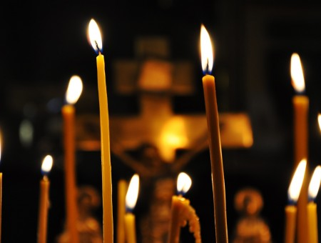 Lighted Candle Sticks With Crucifix In The Background