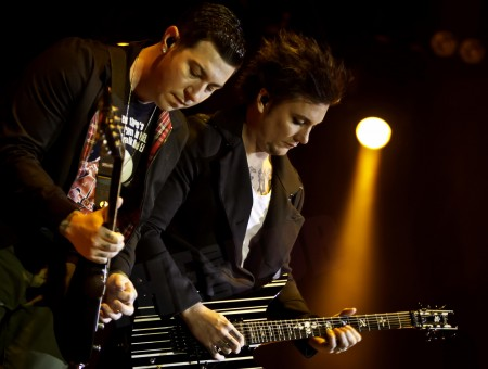2 Men In Black Formal Coat Playing Guitar On Stage