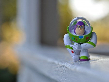 Green And White Buzz Lightyear Kneeling On Window Pane Selective Photo