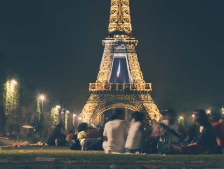 People Sitting On Park Under Eiffel Tower During Night Time