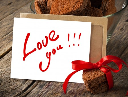 Love You Text On White Card Beside Brownies In Glass Bowl On Brown Wooden Plank