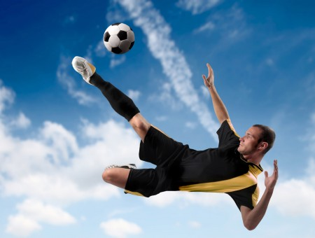 Man Soars On Air Kicking Soccer Ball Under Blue And White Cloudy Sky