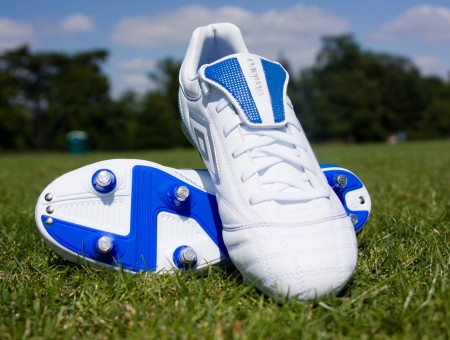 White And Blue Cleat Shoes On Green Grass Surrounded With Green Trees During Daytime