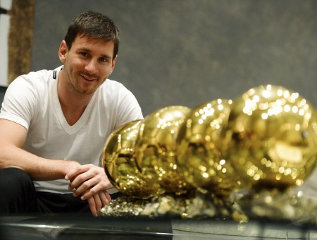 Man In White V Neck T Shirt Smiling And Sitting In Front Of Gold Soccer Ball Trophies On Table