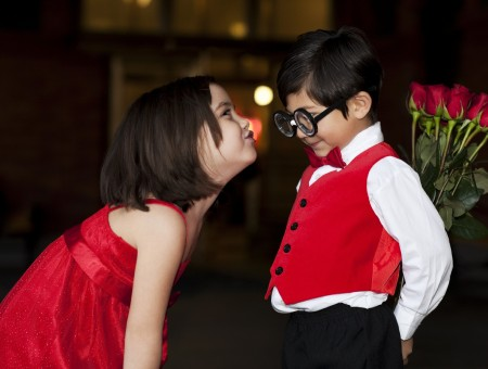 Girl Wearing Red Sleeveless Dress Pouting Lips In Front Of A Boy Wearing Black Framed Eyeglasses And Red Vest