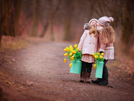 2 Girls Carrying Yellow Roses On Dirt Track In The Woods