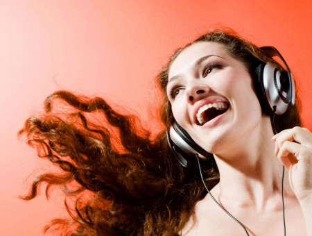 Close Photography Of Woman Wearing Corded Headphone Laughing
