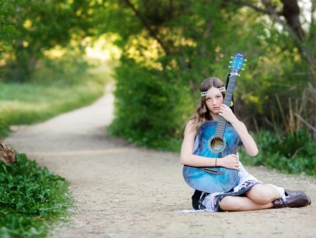 Woman Sitting On Road Holding Blue Acoustic Guitar During Daytime