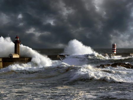 Ocean Waves Striking Lighthouse Under Gray Clouds During Daytime
