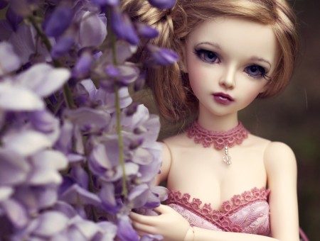 Brown Haired Female Doll Beside White And Purple Flowers