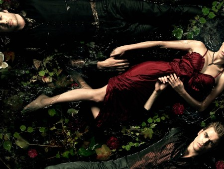 Woman In Red Dress Lying On Green Plants Between Two Men