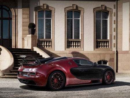 Maroon Black Sports Car Parked Beside Brown Concrete Building