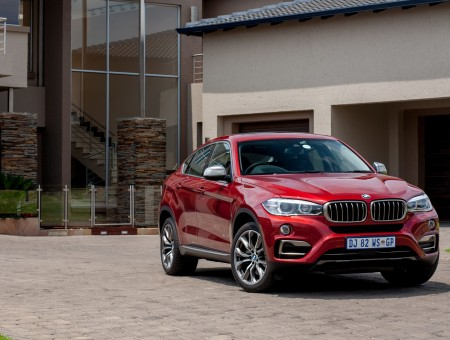 Red BMW X6 On Gray Beside White Concrete Building