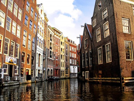 Brown And Orange Building Near Water Canal During Daytime