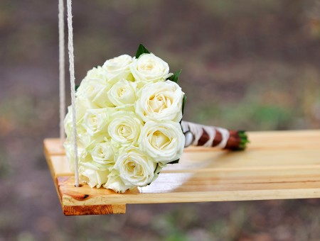 White Rose Bouquet On Brown Wooden Swing