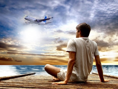 Man In White Shirt And Short Sitting At The Dockside Watching Over A Travelling Airplane In A Blue Sky Background In Panning Photography