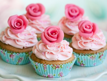 5 Brown Cupcakes With Pink Icing And Pink Flower Candies On White Ceramic Plate