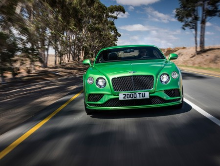 Green Sports Car Traveling On Black Asphalt Road