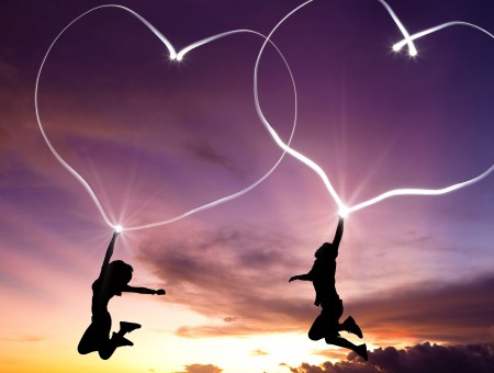 Silhoute Of 2 People Holding A Heart Of Light While Jumping