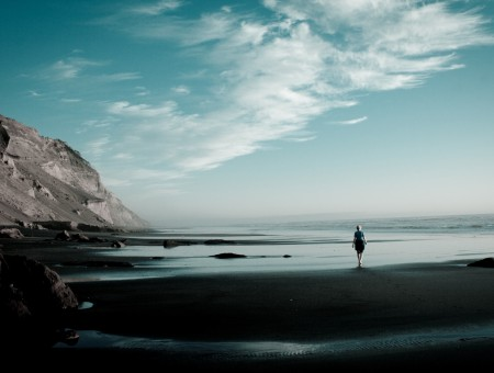 A lonely man walks along the shore