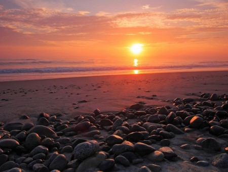 sunset above beach with stones