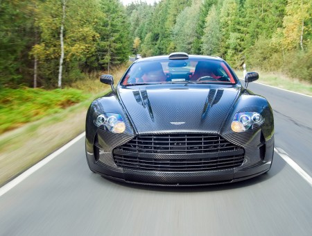 Black race Aston Martin on road