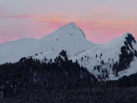 Pink sky above snowy mountains